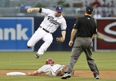San Diego Padres second baseman Jedd Gyorko hurdles Arizona Diamondbacks' Gerardo Parra while trying to catch a wild throw on a successful stolen base during the first inning of a baseball game on Friday, May 2, 2014, in San Diego. Umpire David Rackley, right, watches the play. (AP Photo/Lenny Ignelzi)
