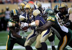 Winnipeg quarterback Drew Willy is wrapped up by Edmonton's Almondo Sewell in the second quarter.