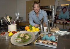 Celebrity chef Curtis Stone poses for a photograph with a meal he cooked of seared scallops and peas with bacon and mint while promoting his new cookbook entitled