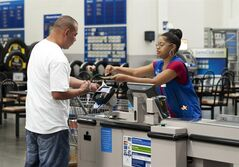 FILE - In this June 5, 2014 photo, Conquisia Tyler, right, gives change to a customer at Sam's Club in Bentonville, Ark. The Commerce Department releases retail sales data for July on Wednesday, Aug. 13, 2014. (AP Photo/Sarah Bentham, File)
