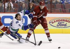 Even after losing his helmet Vancouver Canucks' Zack Kassian (9) goes after the puck against Phoenix Coyotes' Michael Stone (26) during the first period of an NHL hockey game on Thursday, Jan. 16, 2014, in Glendale, Ariz. (AP Photo/Ross D. Franklin)