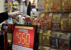 A customer, left, reaches for a Powerball ticket that he purchased in a convenience store in Baltimore.