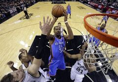 Oklahoma City Thunder's Kevin Durant (35) shoots over San Antonio Spurs' Tim Duncan (21) and San Antonio Spurs' Tiago Splitter, left, during the first half of Game 1 of a Western Conference finals NBA basketball playoff series, Monday, May 19, 2014, in San Antonio. (AP Photo/Eric Gay)