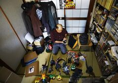 In this Thursday, May 1, 2014 photo, Kazuya Haraguchi, 45, a technician for film reel, responds to a caller in his smartphone with some of his Godzilla collections surrounding him at his apartment in Tokyo. Haraguchi says Hollywood already botched it once with the 1998 remake, directed by Roland Emmerich. And almost everything about the new Godzilla is wrong again, from head to toe - how its arms are limp at its sides, how the scales on its back are too regular, even the shape of its head. (AP Photo/Junji Kurokawa)