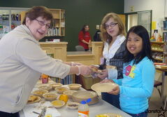 Volunteer Donna de Ridder (left) serves up breakfast for Grade 5 students Ayla Doerksen (centre) Carla Esporlas at Sherwood School.