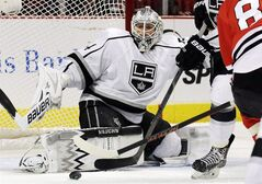 Los Angeles Kings goalie Ben Scrivens, left, blocks a shot by Chicago Blackhawks' Marian Hossa during the second period of an NHL hockey game in Chicago, Sunday, Dec. 15, 2013. (AP Photo/Nam Y. Huh)