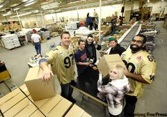 Bombers Doug Brown (97) and Obby Khan (60) help students pack food boxes on Friday for the Christmas Cheer Board.