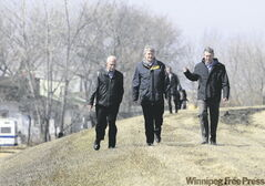 Prime Minister Stephen Harper, with MP Vic Toews (left) and Premier Gary Doer, walks along the Morris dike during a visit to Manitoba Tuesday.