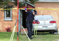 An RCMP officer works at the scene of a suspicious death in MacGregor last Monday.