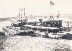 The locomotive the Countess of Dufferin is brought to Winnipeg on a barge towed by the river steamer S.S. Selkirk.
