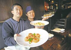 Owners Kaksang Sung, left, and Yun Hee Lee show salmon gateaux, front, takoyaki and shrimp gyoza at Nauru Sushi in Osborne  Village.