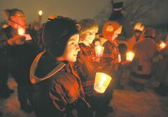 Tobias Scruggs (from left) and cousins Josh and Joel Harder take part in the Torch Light Walk during the opener of the Festival du Voyageur Friday night.
