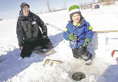 Volunteer Adam Cox with Josh Gadza, 6, who won a fishing rod while learning to ice-fish.