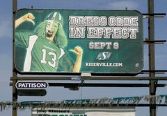 Pro-Roughriders billboard on Route 90 at Silver Avenue urges green dress code for Banjo Bowl.