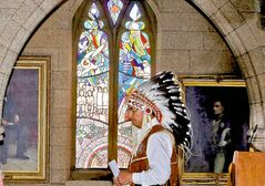 Chief Wilton Littlechild, a commissioner of the Truth and Reconciliation Committee, stand in front of a stained-glass window in the House of Commons foyer.