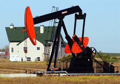 A pump jack dwarfs a house northwest of Calgary, in this Sept. 28, 2004 photo. THE CANADIAN PRESS/Jeff McIntosh