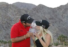 Patrick Reed, left, and wife Justine Reed kiss the trophy at the behest of photographers after the final round of the Humana Challenge PGA golf tournament on the Palmer Private course at PGA West, Sunday, Jan. 19, 2014, in La Quinta, Calif. (AP Photo/Matt York)