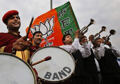 Members of an Indian band perform outside the airport as they wait for the arrival of Bharatiya Janata Party leader and India's next prime minister Narendra Modi in New Delhi, India, Saturday, May 17, 2014. Thousands of cheering supporters welcomed Modi on his arrival in the capital Saturday after leading his party to a staggering victory in national elections. The victory parade came a day after the party crossed the 272-seat majority needed to create a government without forming a coalition with smaller parties. (AP Photo/Manish Swarup)