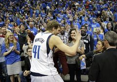 Dallas Mavericks' Dirk Nowitzki (41), of Germany, celebrates with fans after a 113-111 win over the San Antonio Spurs in an NBA basketball first-round playoff series on Friday, May 2, 2014, in Dallas. (AP Photo/Tony Gutierrez)