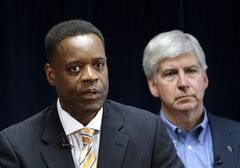 FILE - In this March 14, 2013, file photo, Detroit emergency manager Kevyn Orr, left, speaks at a news conference in Detroit as Michigan Gov. Rick Snyder, who appointed Orr, listens. The Koch Brothers' Americans for Prosperity organization is launching an effort to kill the legislative appropriation that is the key to Detroit's bankruptcy settlement. (AP Photo/Paul Sancya, File)
