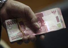 A customer holds a stack of rupiah banknotes at a money changer in Jakarta, Indonesia, Friday, Aug. 23, 2013. Indonesia has announced measures to reduce its current account deficit as Southeast Asia's largest economy suffers a slumping currency and stock market. (AP Photo/Tatan Syuflana)