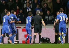 A ball boy, third right, lies on the floor following an incident Chelsea's Eden Hazard, not pictured, as referee Chris Foy, centre in black, makes his way over to calm the situation during the English League Cup second leg semi-final soccer match between Chelsea and Swansea City at the Liberty Stadium, Swansea, Wales, Wednesday Jan. 23, 2013. Hazard received a red card for the incident. (AP Photo/PA, Nick Potts) UNITED KINGDOM OUT NO SALES NO ARCHIVE
