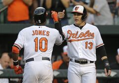 Baltimore Orioles' Manny Machado, right, fist-bumps teammate Adam Jones after Jones batted him in on a home run in the first inning of a baseball game against the Los Angeles Angels, Wednesday, July 30, 2014, in Baltimore. (AP Photo/Patrick Semansky)