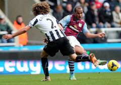 Aston Villa's Gabriel Agbonlahor, right, has a shot towards goal past Newcastle United's captain Fabricio Coloccini, left, during their English Premier League soccer match at St James' Park, Newcastle, England, Sunday, Feb. 23, 2014. (AP Photo/Scott Heppell)
