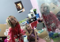 ADVANCE FOR USE TUESDAY, MAY 28, 2013 AND THEREAFTER - With her face reflected in a mirror, Coy Mathis, left, a transgender girl, plays with her sister, Auri, 2, center, at their home in Fountain, Colo. on Monday, Feb. 25, 2013. The parents of Coy Mathis are suing the Fountain-Fort Carson School District 8 after she was denied access to a girl's bathroom at her elementary school. Coy's mother Kathryn Mathis says,