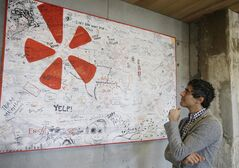 In this photo taken Friday, Aug. 1, 2014, Yelp CEO Jeremy Stoppelman looks over a wall signed by visiting employees from other cities at his company's headquarters in San Francisco. Stoppelman, 36, probably wouldn't be running Yelp Inc. if he had paid more attention to the opinions of outsiders than his own insights. (AP Photo/Eric Risberg)