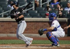 Miami Marlins' Donovan Solano, left, follows through on a ground ball up the third base line to score Adeiny Hechavarria in the third inning of a baseball game against the New York Mets, Saturday, July 12, 2014, in New York. Mets third baseman David Wright was charged with an error on the play. (AP Photo/Julie Jacobson)