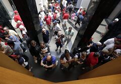 Fans visit the Plaque Gallery at the Baseball Hall of Fame on Saturday, July 26, 2014, in Cooperstown, N.Y. Former Major League Baseball managers Joe Torre, Bobby Cox and Tony La Russa, with pitchers Greg Maddux and Tom Glavine and slugger Frank Thomas, will be inducted to the hall on Sunday. (AP Photo/Mike Groll)