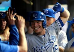 Kansas City Royals' Danny Valencia is congratulated in the dug out after hitting a solo home run in the seventh inning of a baseball game against the Cleveland Indians Saturday July 5, 2014, in Cleveland. (AP Photo/Aaron Josefczyk)