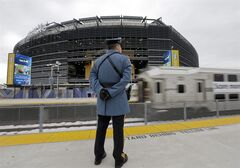 A New Jersey State Trooper stands watch as a train carrying football fans arrives at the Meadowlands Rail Station before the NFL Super Bowl XLVIII football game Sunday, Feb. 2, 2014, in East Rutherford, N.J. (AP Photo/Gregory Bull)