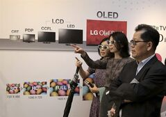 Visitors wearing 3-D glasses look at LG Electronics' Ultra Organic Light-emitting Diode (OLED) 3D TVs during a press unveiling in Seoul, South Korea. Monday, Aug. 25, 2014. LG Electronics Inc. is sticking with its strategy of using the exceptionally expensive OLED display technology for TVs, announcing two new giant models with ultra-high definition screens. (AP Photo/Ahn Young-joon)
