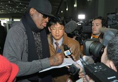Former NBA star Dennis Rodman signs his autograph for a fan at the Pyongyang Airport in Pyongyang, before he leaves North Korea Friday, March 1, 2013. Ending his unexpected round of basketball diplomacy in North Korea on Friday, Rodman called leader Kim Jong Un an