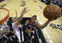 Portland Trail Blazers' LaMarcus Aldridge (12) shoots past San Antonio Spurs' Kawhi Leonard (2) during the first half of Game 2 of a Western Conference semifinal NBA basketball playoff series, Thursday, May 8, 2014, in San Antonio. (AP Photo/Eric Gay)
