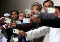 FILE - This Saturday June 14, 2014 file photo shows Afghan men displaying their identification cardsas they wait in line at a polling station in Kabul to vote for the next president of Afghanistan. The peace process is with the Taliban in Afghanistan is virtually on hold until it's clear who that will be. It's also unclear what role the Obama administration can or is willing to play to coax the Taliban to the negotiating table. (AP Photo/Gulbuddin Elham, File)