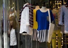 A woman walks out of a fashion boutique at a shopping mall in Beijing Monday, May 5, 2014. China's manufacturing contracted in April for the fourth straight month but the pace of decline was less severe, suggesting the downturn in the world's No. 2 economy is bottoming out. (AP Photo/Andy Wong)