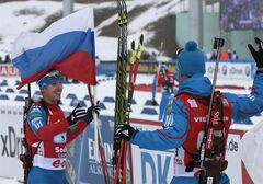 Russian team member Evgeny Ustyugov,left, with Russian national flag, celebrates the teams win together with a team member after crossing the finish line in the men's 4X7,5 km Relay at the Laura Biathlon stadium in the Olympic mountain cluster during the IBU World Cup Biathlon in Sochi, Russia, Sunday, March 10, 2013. (AP Photo/Mikhail Metzel)