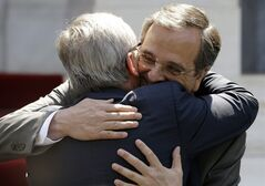 Greece's Prime Minister Antonis, right, hugs Jean-Claude Juncker, president-elect of the European Commission at the Maximos Mansion in Athens, Monday, Aug. 4, 2014. Juncker is visit Athens in his first trip since his election by the new European Parliament last month. He meets Samaras, a fellow conservative, to express support for the country's ongoing effort to make its public finances sustainable. (AP Photo/Thanassis Stavrakis)