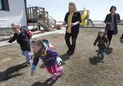 Heather Campbell-Dewar (left) and Nancy Vardalos Ginakes with friends' children (ltor) Bode Lynch, Whitley Monforton and Ivy Cooper demonstrate the Safe2Go harnesses.