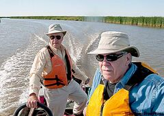 Dennis (left) and brother Jim Anderson investigate the rising water levels while on their boat near the Netley-Libau wetland.