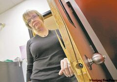 Michele Visser shows a door damaged during a break-in at the Indian Family Centre on Friday.