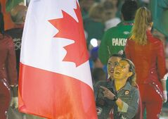 Christine Sinclair carries the Canadian flag into the  Olympics'  closing  ceremonies Sunday.