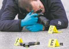 Police officer snaps pistol, shell casing on Stafford Street after the Salisbury House killing Sept. 27.