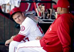 Los Angeles Angels teammates Mike Trout (left) and Albert Pujols have a chat in the dugout.