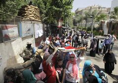 Voters line up as some take shade under a national flag outside a polling station to vote for president in an election that comes nearly a year after the military's ouster of the nation's first freely elected president, the Islamist Mohammed Morsi in Cairo, Egypt, Monday, May 26, 2014. The man who removed Morsi, retired military chief Field Marshal Abdel-Fattah el-Sissi, is practically assured of a victory in the vote.(AP Photo/Amr Nabil)