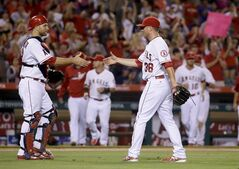 Los Angeles Angels catcher Chris Iannetta, left, and relief pitcher Joe Smith celebrate their win 5-2 against the Houston Astros in a baseball game in Anaheim, Calif., Thursday, July 3, 2014. (AP Photo/Chris Carlson)