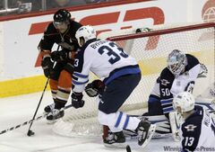 The Anaheim Ducks' Teemu Selanne (8) tries to wrap the puck around the Winnipeg Jets' net while Dustin Byfuglien (33) moves to intercept him in the first period at the MTS Centre on Saturday night.